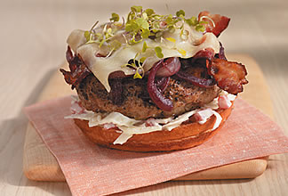 Grilled Australian lamb burger with red wine-braised onions, applewood-smoked bacon and swiss cheese topped with apple fennel yogurt remoulade