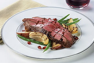 Pomegranate glazed flank steak on potato wedges and beans