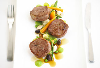 Seared lamb medallions with almond and mint pea cream and baby vegetables