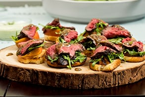 Mustard glazed beef tenderloin with peach and arugula bruschetta